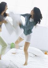 Zwei junge Frauen kämpfen mit Kissen, verschwommen motion