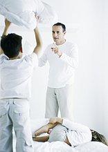 Stehend auf Bett hält Kissen, Rückansicht, zweite Boy liegen auf dem Bett, Mann pointing am ersten Boy Boy