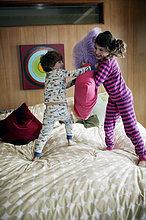 Jungen und Mädchen (4-8) im Pyjama mit Kissen kämpfen auf dem Bett
