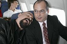 Businessman Sitting in einem Flugzeug gefangen von einem Mann an seiner Seite schlafen