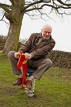 70 Jahre alter Mann mit Spaß in einem Kinderspielplatz