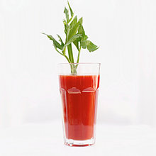 Nahaufnahme eines Glases Tomatensaft garniert mit einem Stock Sellerie