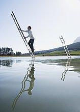 Man Klettern Leiter im Wasser