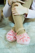 Teenagermädchen umarmt Knie, trägt Strumpfhosen und Pantoffeln, abgeschnittene Ansicht der Beine