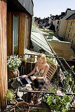 Frau sitzt auf dem Balkon