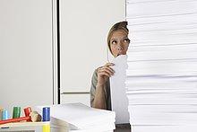Junge Frau, die von zu Hause aus mit einem riesigen Stapel Papier arbeitet.