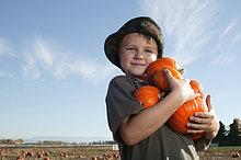 Portrait eines jungen (6-7) mit kleinen Kürbisse in Felder, lächelnd