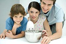 Vater und zwei Kinder beim gemeinsamen Backen, alle lächelnd vor der Kamera