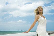 Junge Frau gelehnt gegen Ledge mit Augen geschlossen, Wind weht Haare über Gesicht, lächelnd