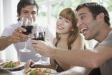 Drei Personen toasting Rotwein am Tisch und lächelnd