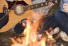 Close up of Lagerfeuer mit Leute sitzen gekreuzten Beinen spielte Gitarre - headless