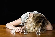 Eine junge Frau ohnmächtig betrunken auf eine Bar Counter