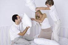 Eltern und jungen Sohn mit Kissen kämpfen auf dem Bett