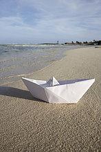 Papierboot auf sandigen Strand liegend