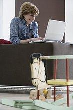 Interior, zu Hause ,Frau ,Computer ,Notebook ,arbeiten ,Fokus auf den Vordergrund, Fokus auf dem Vordergrund ,jung