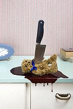 Messer, das einen Teddybären auf eine Kommode sticht.