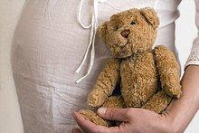 Mitte Schnittansicht schwangeren Frau hält Teddybär