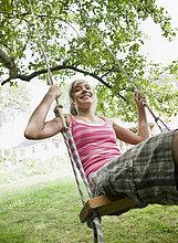 Junges Mädchen auf einer Baumschaukel
