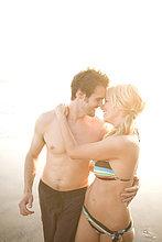 Paar in Badeanzüge umarmt am Strand