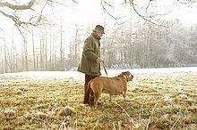 Seitenansicht ein älterer Mann zu Fuß mit einen Hund im park