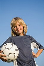 Boy posing with football under arm