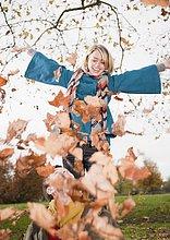 Frau spielt mit Laub in herbstlichem Park
