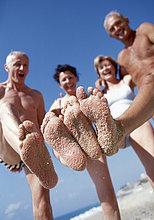 Zwei Seniorenpaare am Strand mit Sand an Füßen