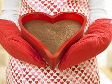 Frau hält herzförmigen Kuchen