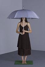 Weibchen steht unter Schirm auf Kunstrasen, Gesicht teilweise verdunkelt