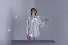 Mann steht mit ausgestreckter Hand, schaut nach oben, Papierkugeln in der Luft um ihn herum.