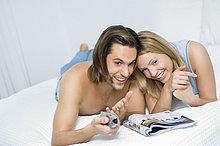 Junges Paar liegt auf Bett und sieht zusammen fern, lachen