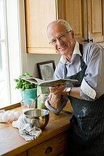 älterer Mann dabei, Kochen, lesen ein Kochbuch, Schweden.