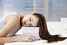 Geschäftsfrau schläft auf Stapel von Papieren
