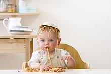 Chaotisch männliches Baby in Hochstuhl mit Schüssel Spaghetti auf Kopf