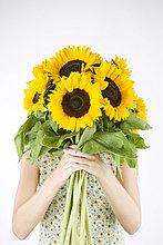 Eine junge Frau hinter eine frische Sonnenblumen im Strauss