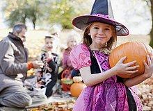 Mädchen in Halloween-Kostüm hält Kürbis