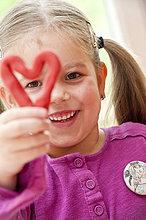Kleines Mädchen hält ein selbstgemachtes Herz in die Kamera, Porträt