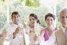 Glückliche Familie auf einer Hochzeitsfeier stößt mit Champagner an