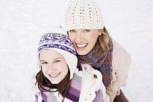 Mutter und Tochter umarmen sich im Schnee
