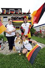 Fans der deutschen Nationalmannschaft in Nationaltrikots mit Deutschlandflaggen vor geschmücktem Wohnhaus, Stuttgart, Baden-Württemberg, Deutschland, Europa
