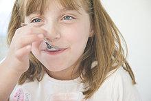 Junges Mädchen essen mit Teelöffel
