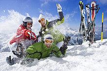 Skier im Schnee und Familie mit Schneeballschlacht auf dem Berggipfel