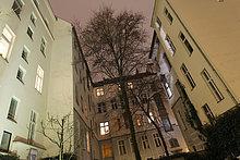 Hinterhof mit beleuchteten Fenstern an der Kantstraße in Charlottenburg, Berlin, Deutschland
