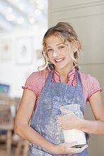 Lächelndes Mädchen mit Mehl auf der Nasenspitze hält Glas