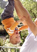 Menschlicher Vater ,Sohn ,halten ,kopfüber
