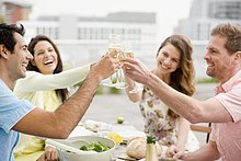 Laughing couples toasting with Champagne outdoors