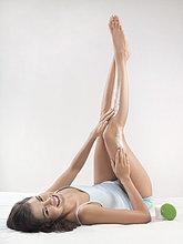 Junge Frau Bein Feuchtigkeitscreme zuweisen