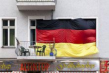 Riesige Deutschlandfahne verdeckt die Fenster zu einer Wohnung, mit Balkon, darunter Imbiss mit Grillhähnchen, Oberschöneweide, Berlin, Deutschland, Europa