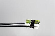 Schwarze Essstäbchen halten Nigiri-Sushi mit grünem Spargel, umwickelt mit Nori