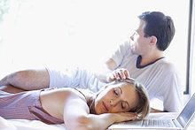 Frau mit ihrem Mann neben ihr auf dem Bett schlafen